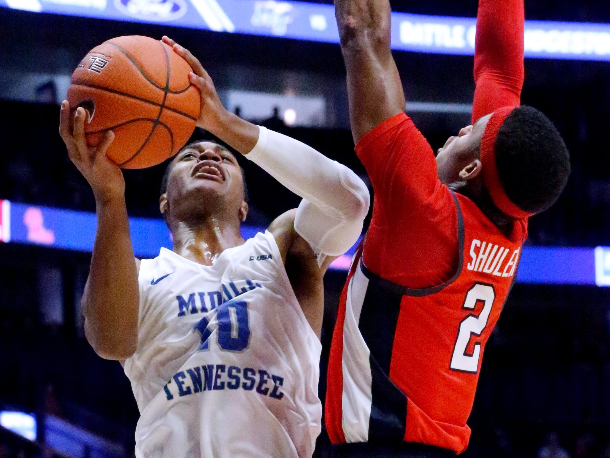 MTSU's guard Jayce Johnson (10) shoots the ball as Ole Miss' guard Devontae Shuler (2) guards him on Friday Dec. 21, 2018, at Bridgestone Arena.