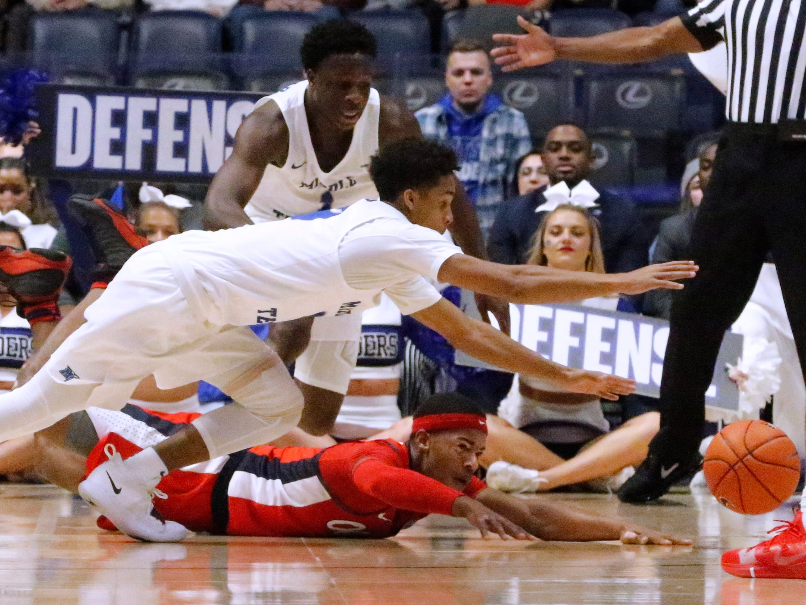 MTSU's guard Donovan Sims (3) and Ole Miss' guard Devontae Shuler (2) and MTSU's guard Junior Farquhar (1) all go for a loose ball on Friday Dec. 21, 2018, at Bridgestone Arena.