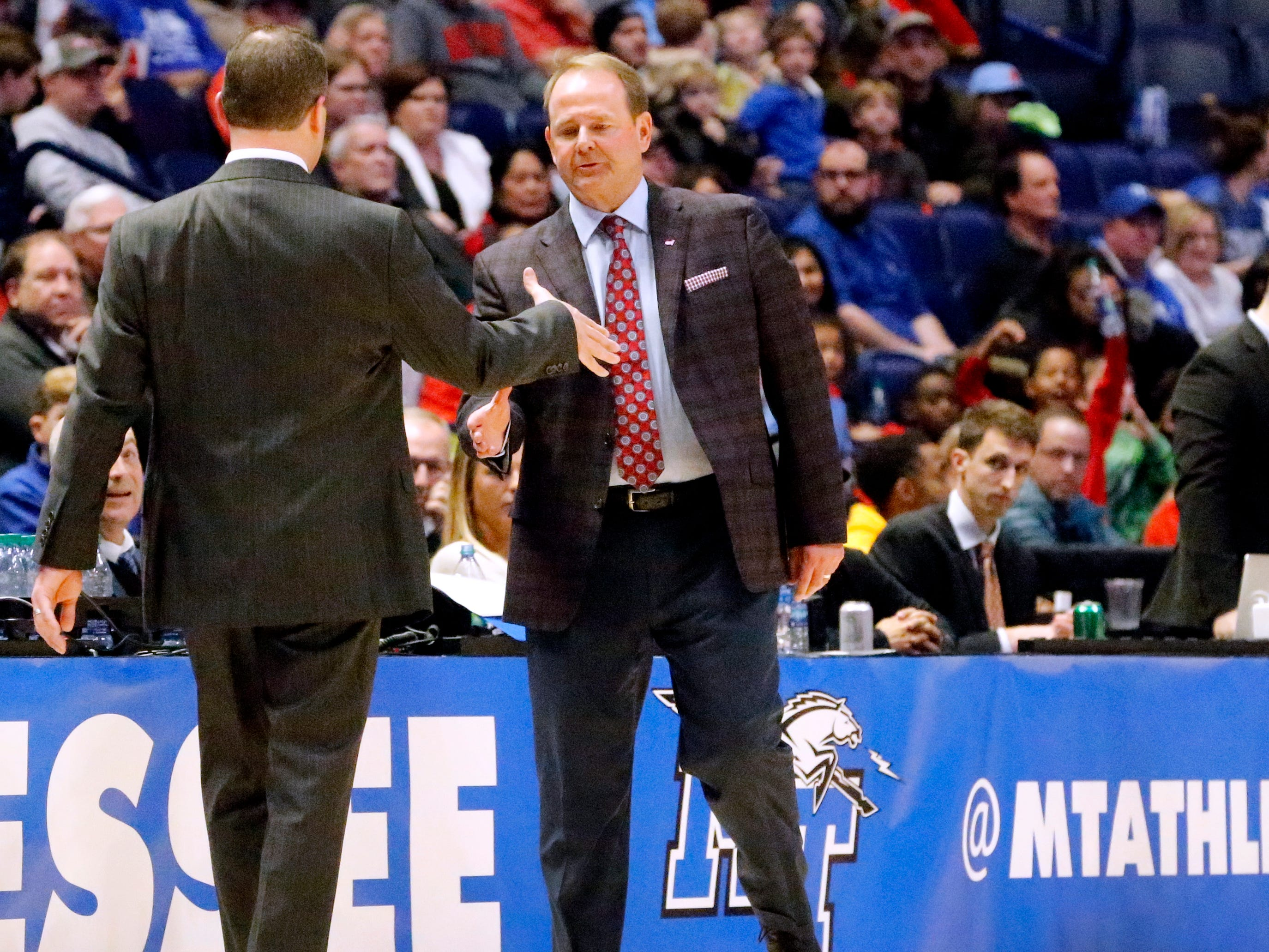 MTSU's head coach Nick McDevitt, left and Ole Miss' head coach Kermit Davis, right meet in the middle of the sidelines after MTSU loses two Ole Miss 74-56, on Friday Dec. 21, 2018, at Bridgestone Arena.