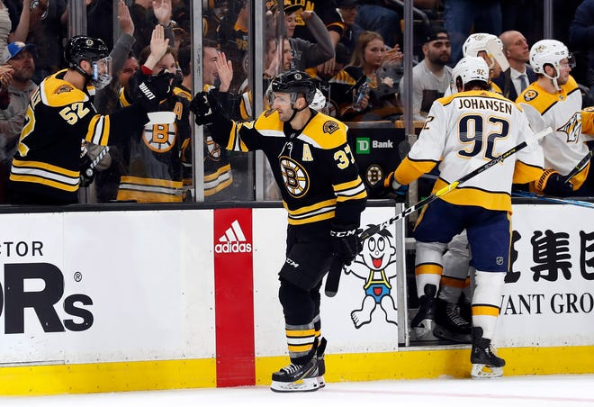 Bruins center Patrice Bergeron (37) is congratulated after scoring as Predators center Ryan Johansen (92) heads to the bench during the first period Saturday at TD Garden.