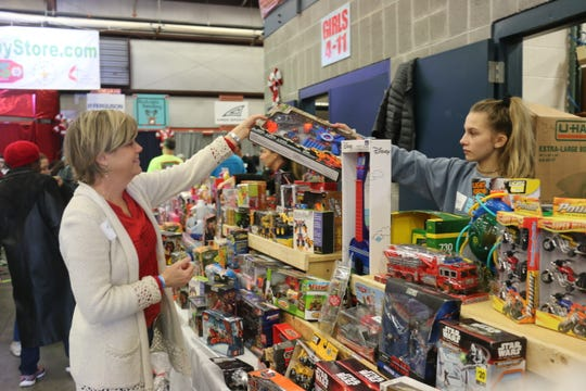 Tiffany Baur and Phebe Nola set up the toy table at the Last Minute Toy Store on Dec. 22, 2018.