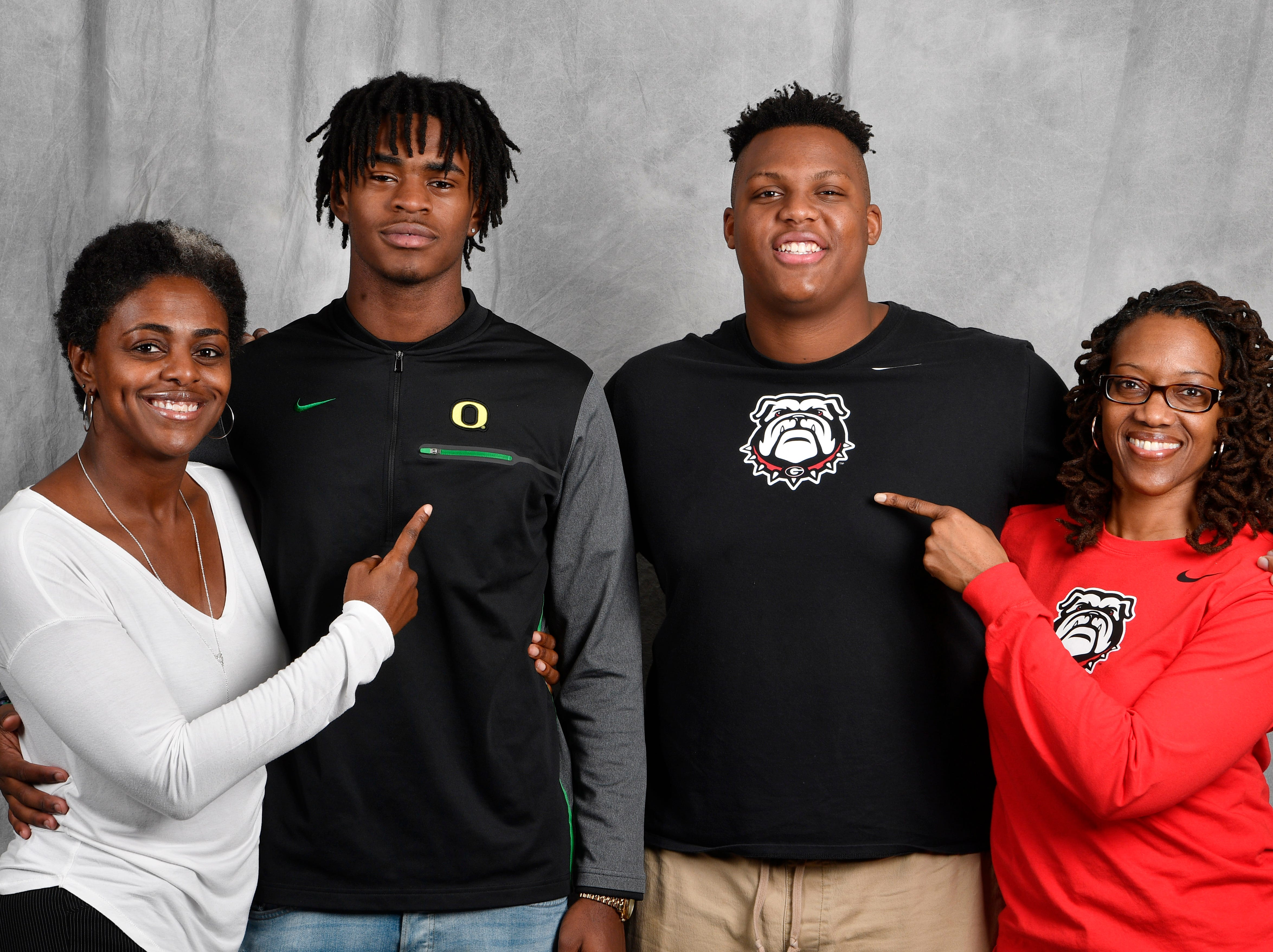 FRA's Lance Wilhoite and Tymon Mitchell pose with their moms in the Tennessean's photo booth on the first day of the early signing period. From left, are Travonya Wilhoite, Lance Wilhoite, Tymore Mitchell and Andrea McClain. Lance signed with Oregon to play football while Tymon signed with Georgia.