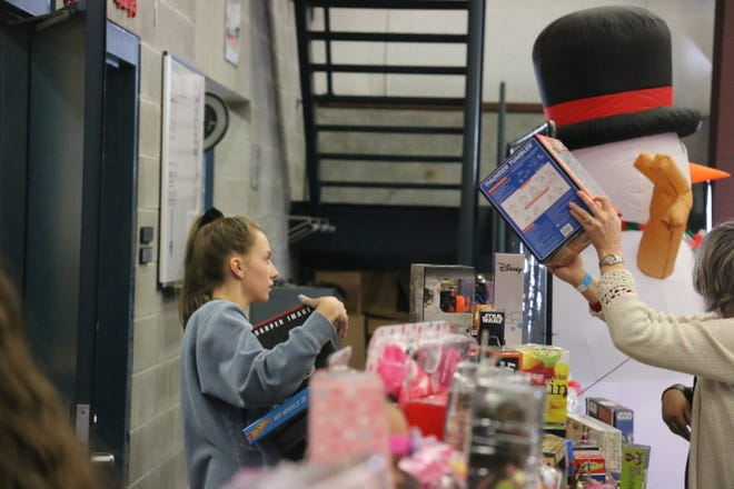 Phebe Baur, 15, helps arrange the toy table at the Last Minute Toy Store on Dec. 22, 2018.