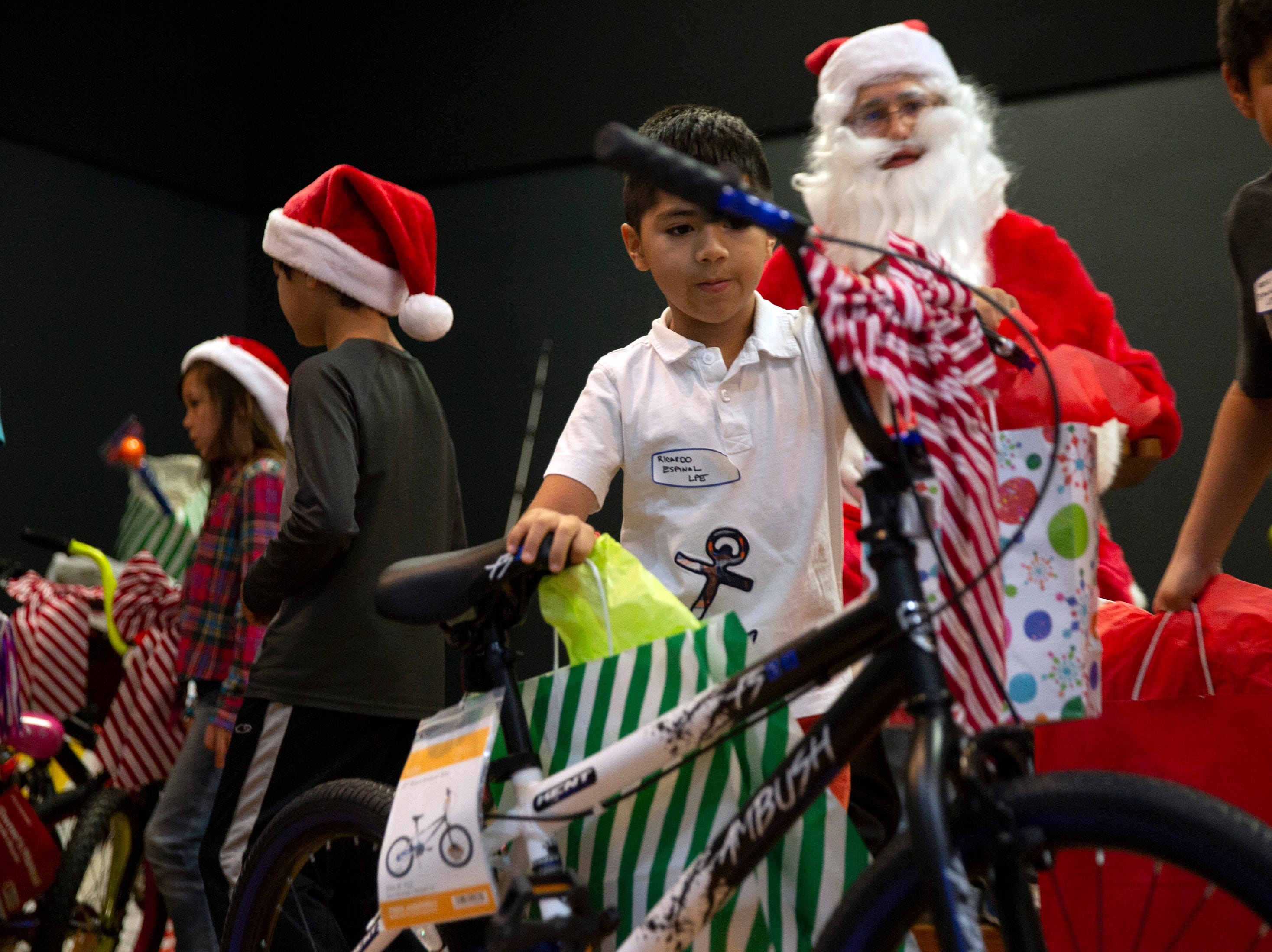Pedro Espinal Martinez looks over his brand new bike given to him during a charitable event hosted by the Fraternal Order of Police, Lodge 38 at the River Park Community Center, Saturday, Dec. 22, 2018 in Naples.