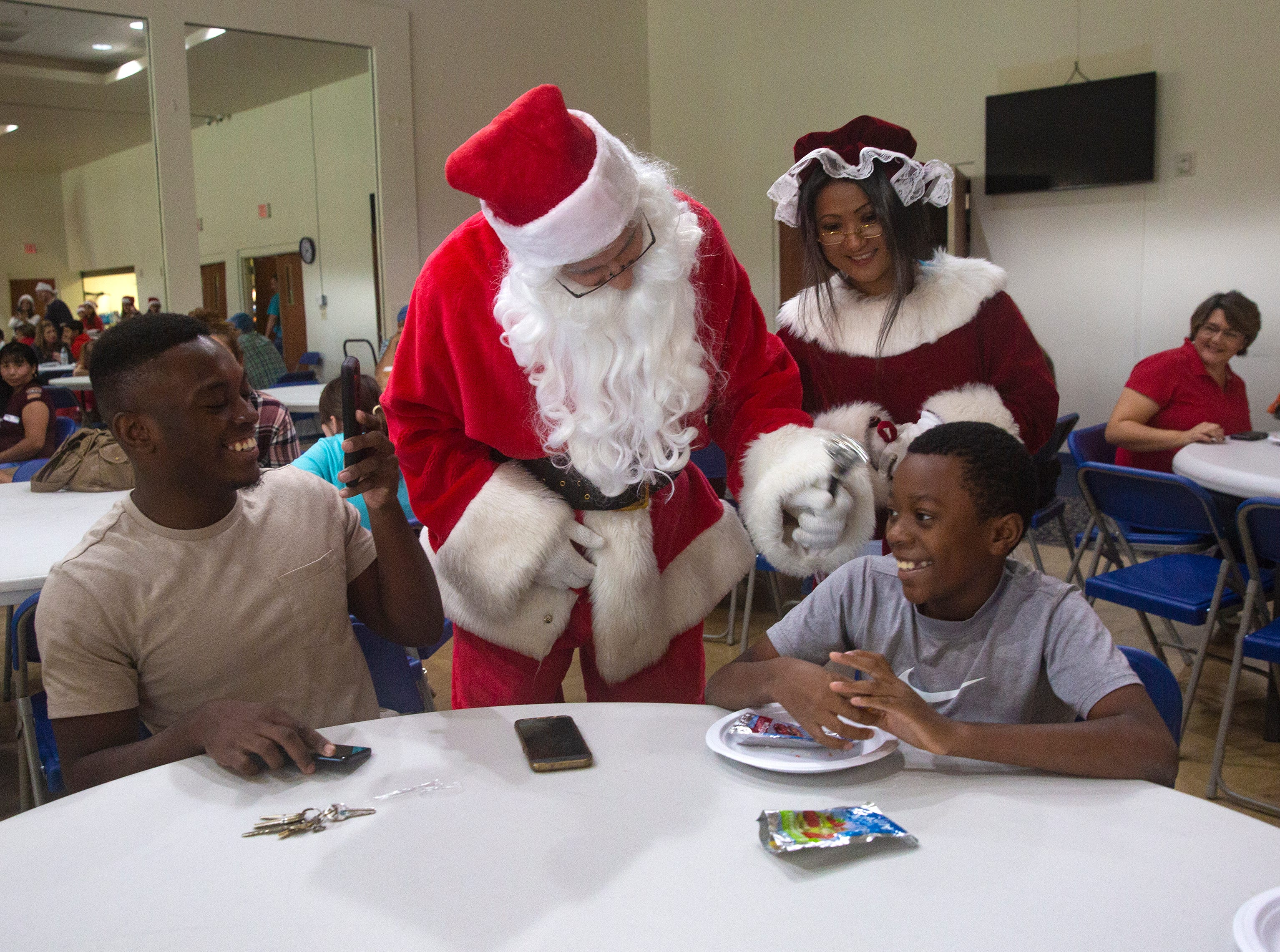Hervangelot Lordeus, left, and his brother Delyn Jorame share a conversation with Mr. and Mrs. Santa Claus played  by Benny Vasquez and his wife Kelly Vasquez during a charitable event hosted by the Fraternal Order of Police, Lodge 38 at the River Park Community Center, Saturday, Dec. 22, 2018 in Naples.