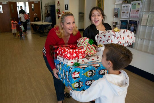 Katia Noda and her children Arianna Noda and Arian Noda, bottom, carry out their Christmas presents presented to the children during a charitable event hosted by the Fraternal Order of Police, Lodge 38 at the River Park Community Center, Saturday, Dec. 22, 2018 in Naples.