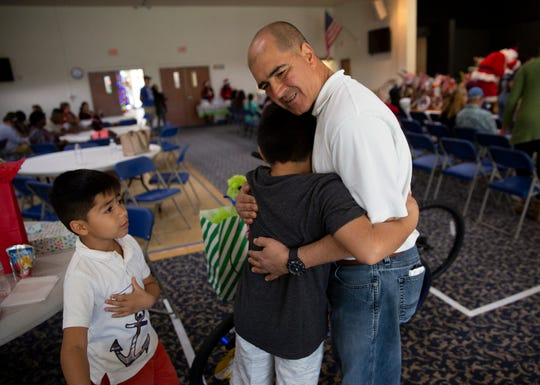 Pedro Espinal Martinez Sr., gets a thank-you hug from his sons Pedro Espinal Martinez, center, and Ricardo Espinal Martinez, after the brothers received gifts during a charitable event hosted by the Fraternal Order of Police, Lodge 38 at the River Park Community Center, Saturday, Dec. 22, 2018 in Naples.