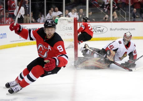 Ottawa Senators goaltender Craig Anderson right, watches as New Jersey Devils left wing Taylor Hall (9) celebrates after scoring a goal during the second period of an NHL hockey game, Friday, Dec. 21, 2018, in Newark, N.J.