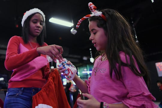 Bill Cuello organized a photo shoot with Santa for hundreds of families in Passaic, NJ, at no cost to them. Santa visits the Fiesta Club in Passaic on Saturday December 22, 2018. Dayamaris Cuello hands out goodies to Vareree Valazquez.