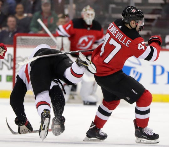 Ottawa Senators defenseman Thomas Chabot, left, loses his balance while competing for the puck with New Jersey Devils center John Quenneville (47) during the second period of an NHL hockey game Friday, Dec. 21, 2018, in Newark, N.J.