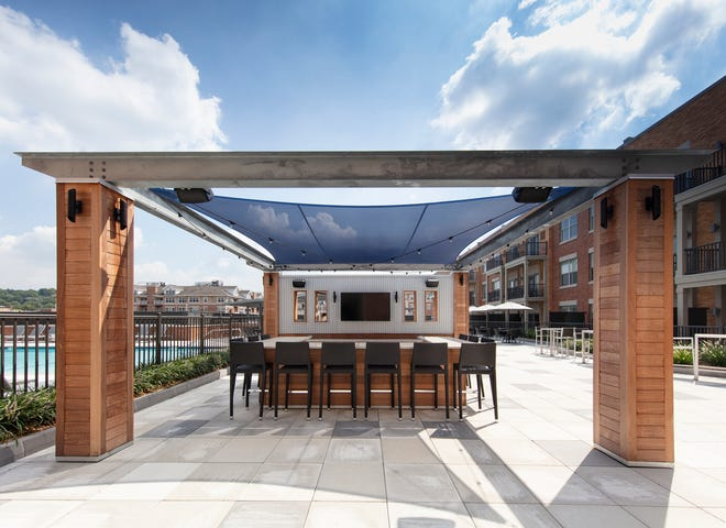 Residents have plenty of recreational and social amenities to enjoy, like an outside bar with TV, at One William, the luxury rental community in Englewood, NJ.