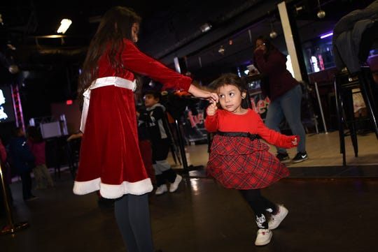 Bill Cuello organized a photo shoot with Santa for hundreds of families in Passaic, NJ, at no cost to them. Santa visits the Fiesta Club in Passaic on Saturday December 22, 2018. Yehudi Velazquez, 10, and her sister Zully Velazquez, 2, dance.