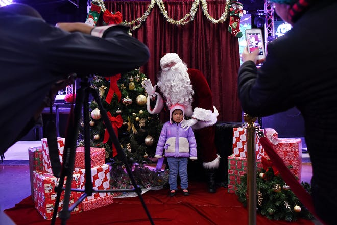 Bill Cuello organized a photo shoot with Santa for hundreds of families in Passaic, NJ, at no cost to them. Santa visits the Fiesta Club in Passaic on Saturday December 22, 2018. A child poses for photos with Santa.