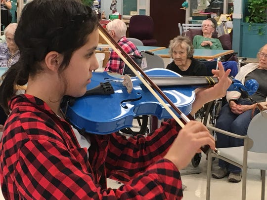 Ethni Florez, 11, plays the violin at Lakeview Nursing Home.