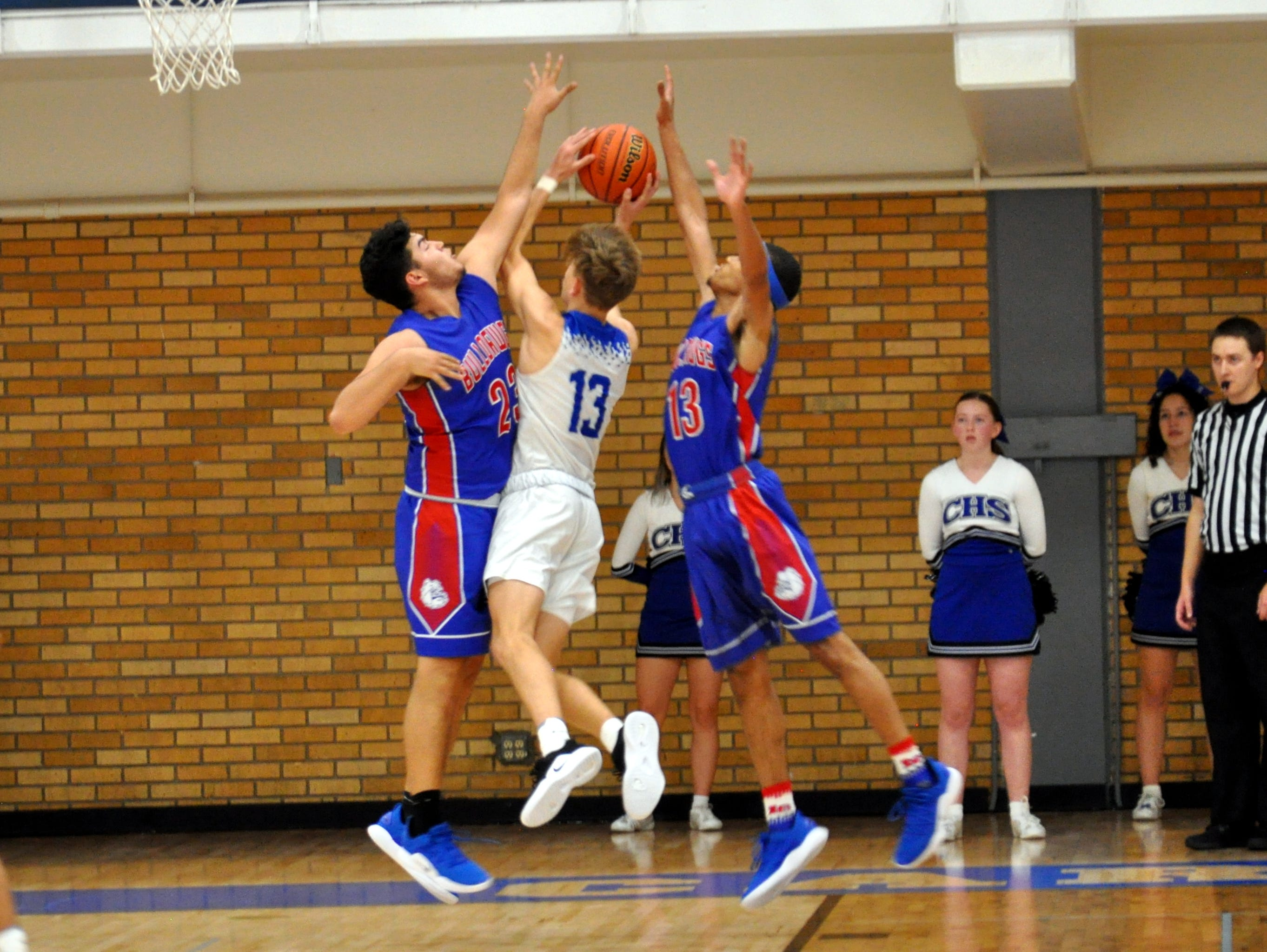 Las Cruces' Sal Nevarez, left, and Ray Brown, right block Stevie Bartlett's, center, shot attempt during Friday's game.