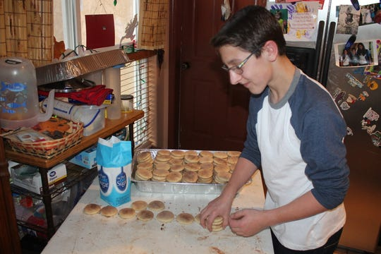Susan Flores' grandson Max stacks biscochitos, a fraction of the 1,600 distributed free to neighbors.