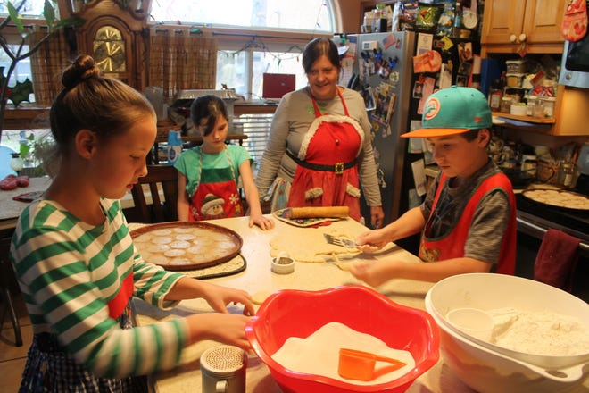 Susan Flores and her grandkids Mary, Amelia and Max prepare a batch of biscochitos to hand out to free to neighbors. It's a family tradition that has spanned years.