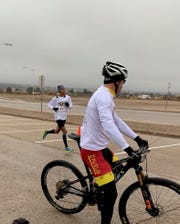 Julia Florez coming in to the finishing line, with Kevin Quattlebaum as pacer bicyclist for the race.