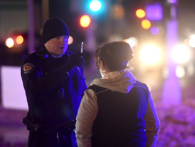 Farmington Police Department Sgt. Brian Johnston conducts a field sobriety test on Jan. 13, 2016, after responding to a car crash on Butler Avenue between East Main Street and East Broadway Avenue.