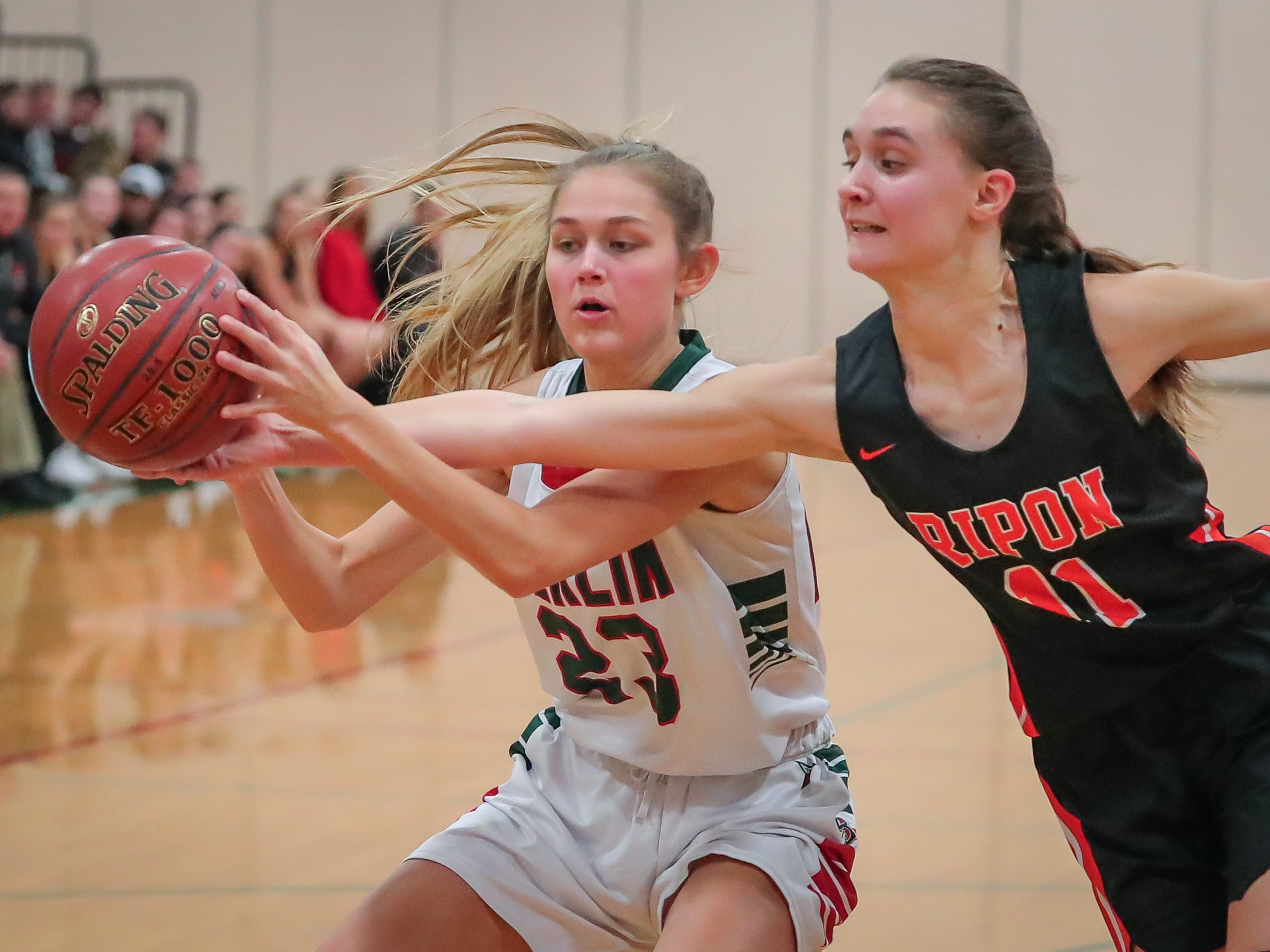 Alexa Miller (11) tries to tip the ball out of the hands of Emily Klawitter (23) of Berlin. The Berlin Indians hosted the Ripon Tigers in an East Central Conference girls basketball matchup Friday evening, December 21, 2018.