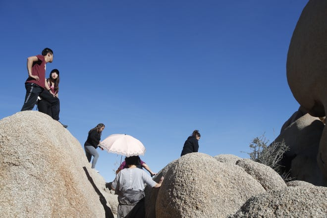 People enjoy Skull Rock formations in Joshua Tree National Park. The popular park remains technically open, though only a skeleton crew is managing it during the federal government shutdown.
