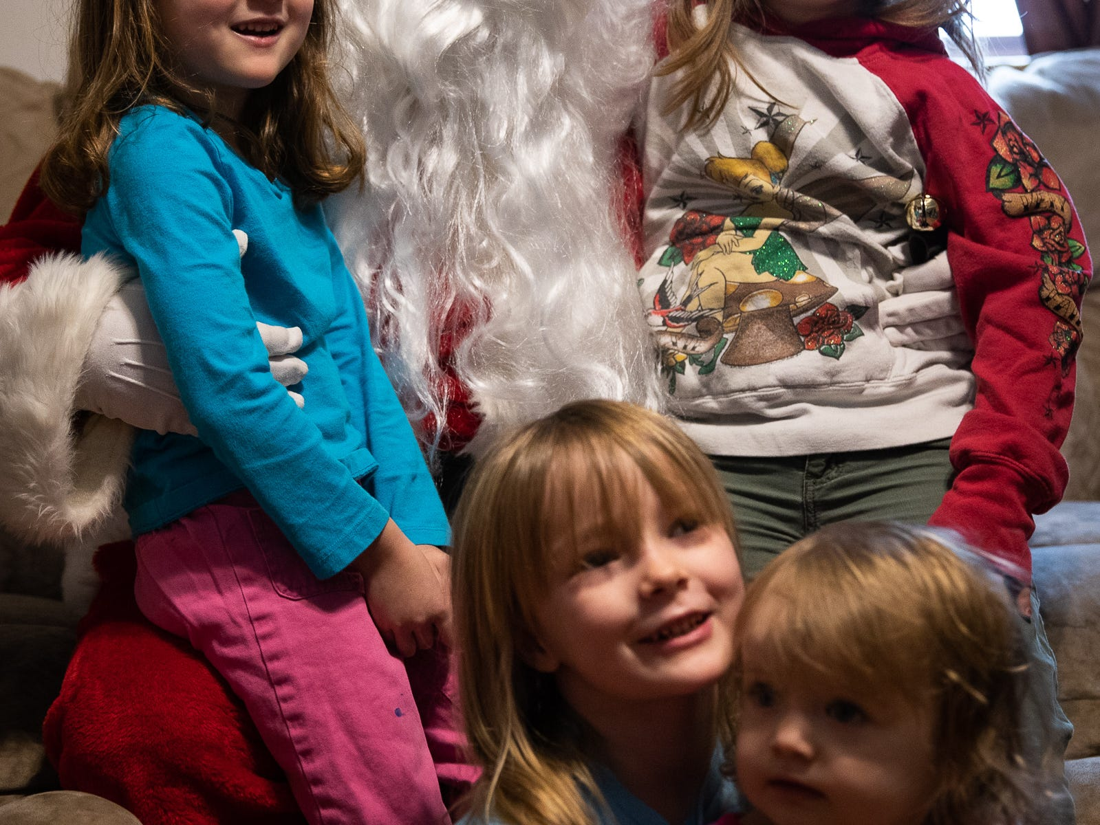 Mia, 4, back left, Sierra, 7, back right, Laila, 6, front left, and Arianna, 2, front right, pose for a photo with Santa, played by firefighter Wayne Reid, during the S.A.V.E.S Project Santa, Saturday, Dec. 22, 2018, in McSherrystown Borough. The S.A.V.E.S Project Santa donated food, toys, and clothing to 12 local families in need.