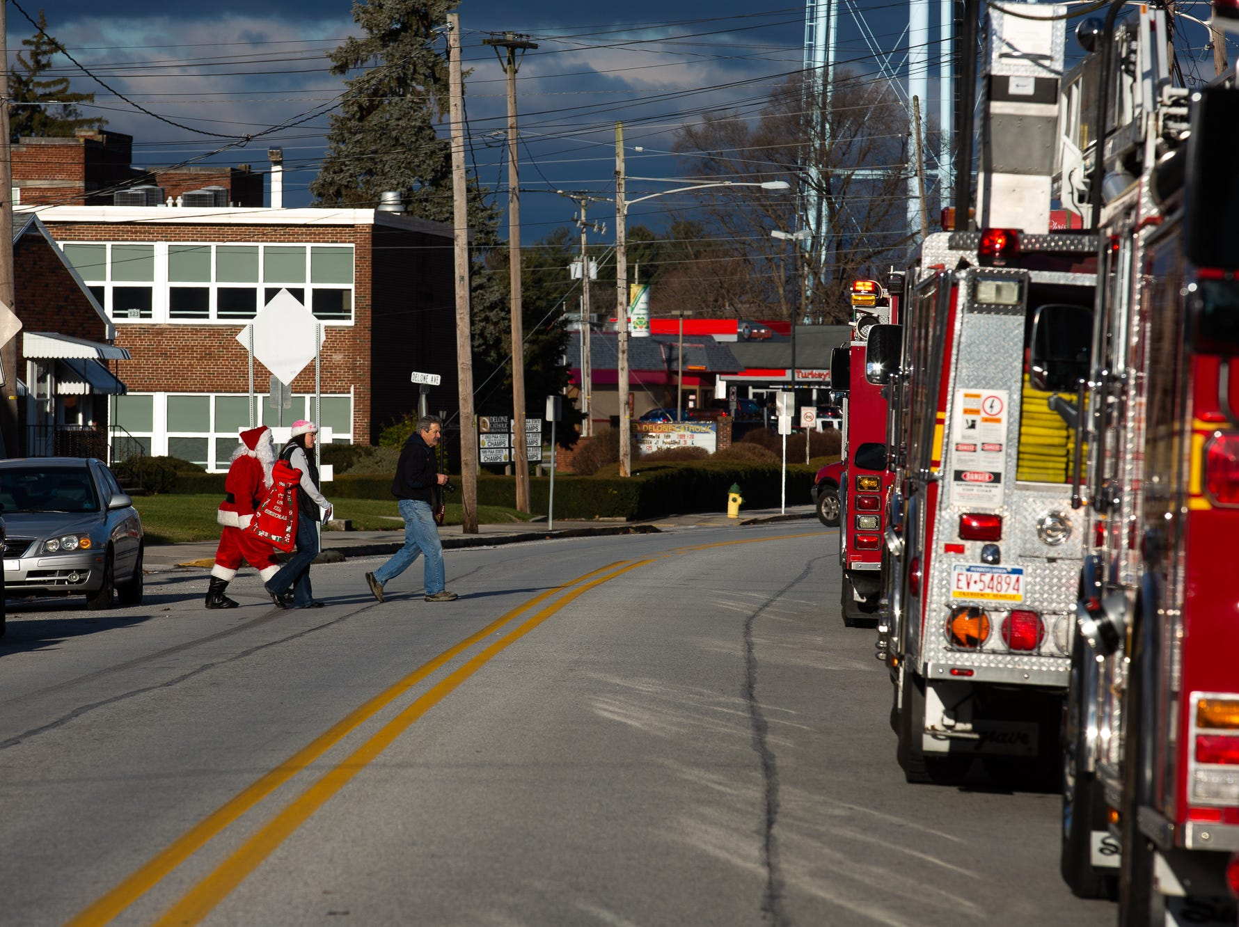 Santa, played by firefighter Wayne Reid, crosses 3rd St. during the S.A.V.E.S Project Santa, Saturday, Dec. 22, 2018, in McSherrystown Borough. The S.A.V.E.S Project Santa donated food, toys, and clothing to 12 local families in need.
