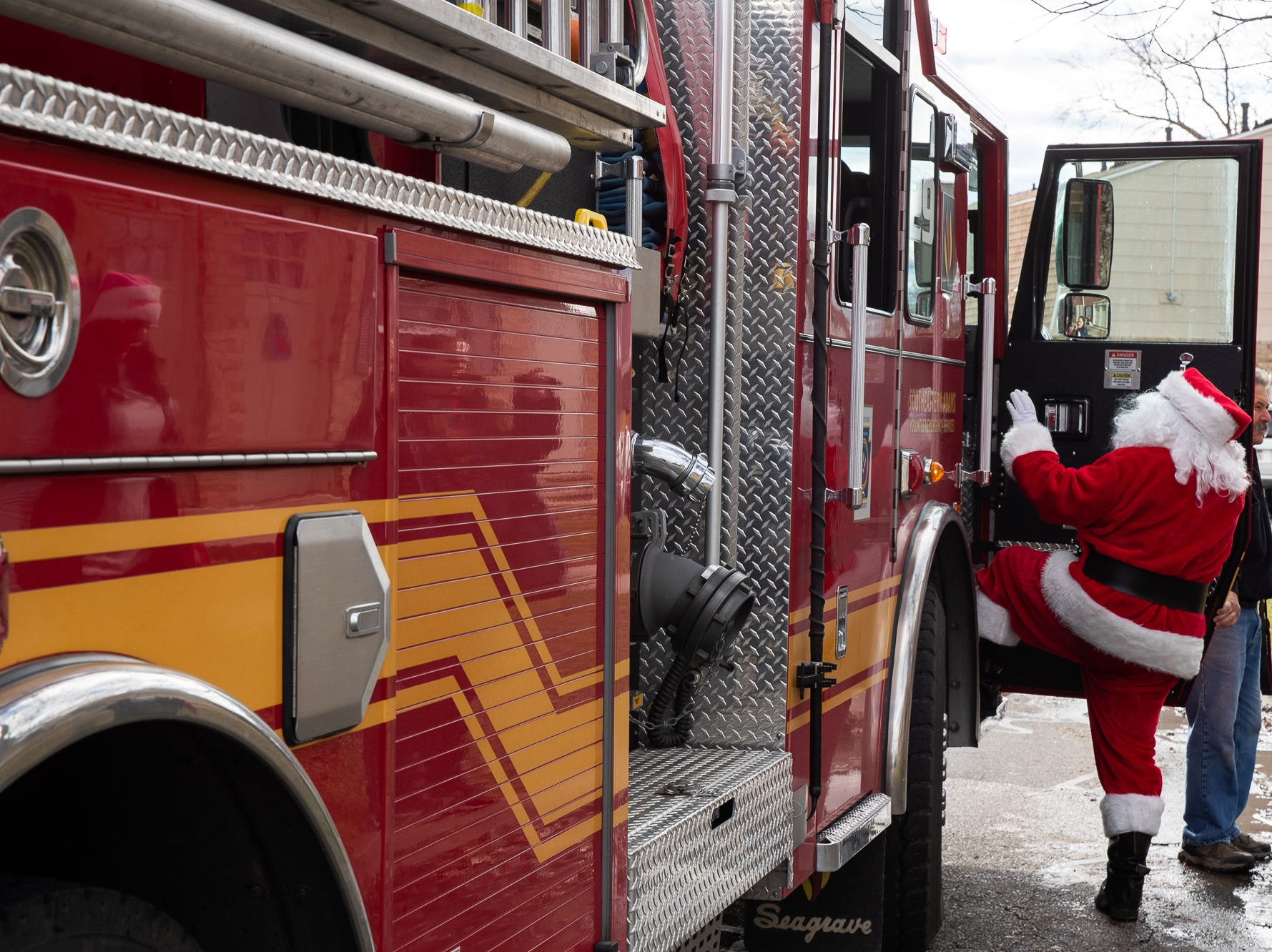 Santa, played by firefighter Wayne Reid, hops on his fire engine during the S.A.V.E.S Project Santa, Saturday, Dec. 22, 2018, in McSherrystown Borough. The S.A.V.E.S Project Santa donated food, toys, and clothing to 12 local families in need.