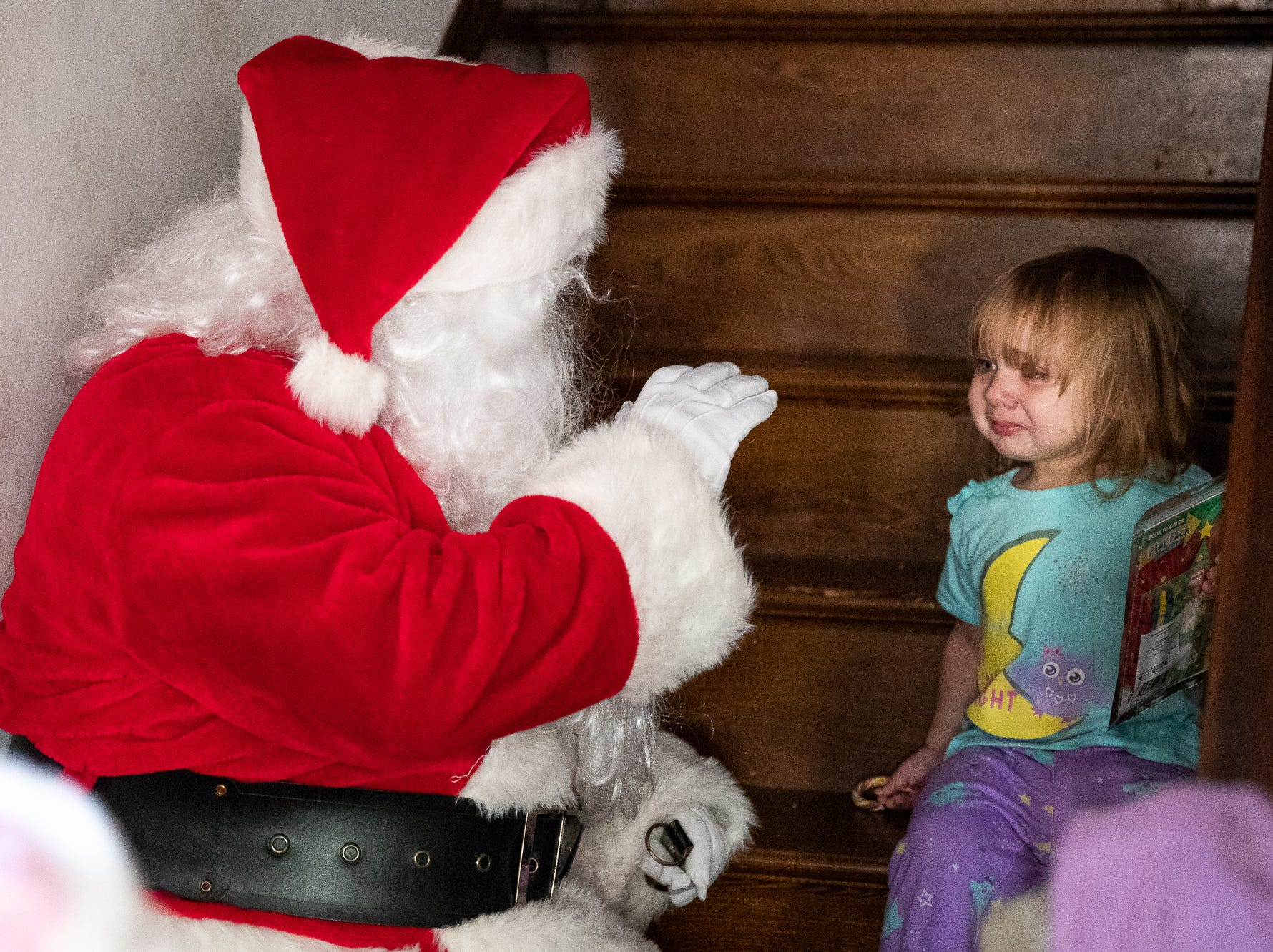 Sofia, 2, reacts to Santa, played by firefighter Wayne Reid, during the S.A.V.E.S Project Santa, Saturday, Dec. 22, 2018, in McSherrystown Borough. The S.A.V.E.S Project Santa donated food, toys, and clothing to 12 local families in need.
