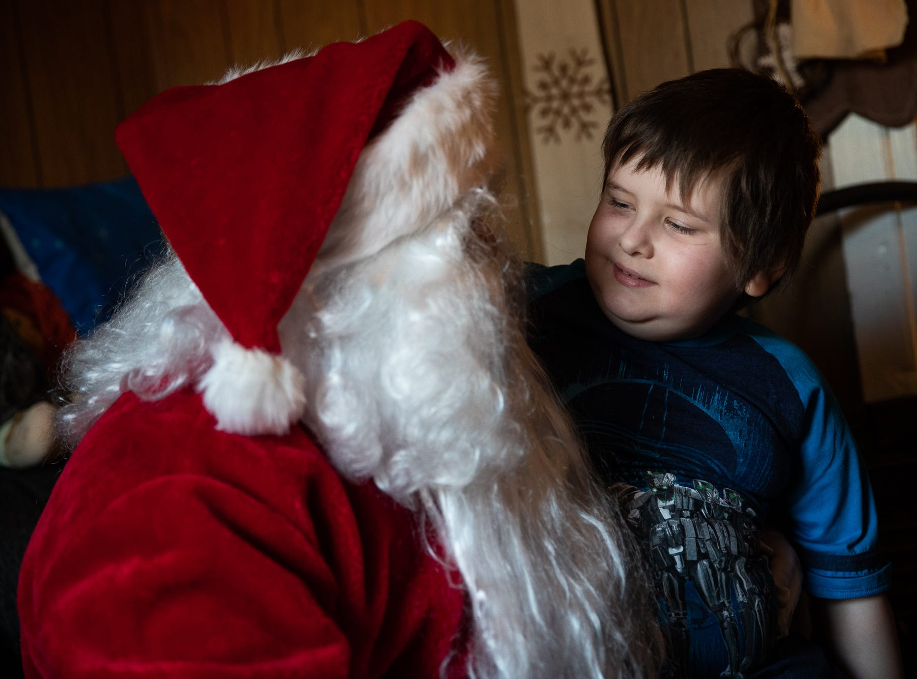Raphael, 8, sits on the lap of Santa, played by firefighter Wayne Reid, during the S.A.V.E.S Project Santa, Saturday, Dec. 22, 2018, in McSherrystown Borough. The S.A.V.E.S Project Santa donated food, toys, and clothing to 12 local families in need.