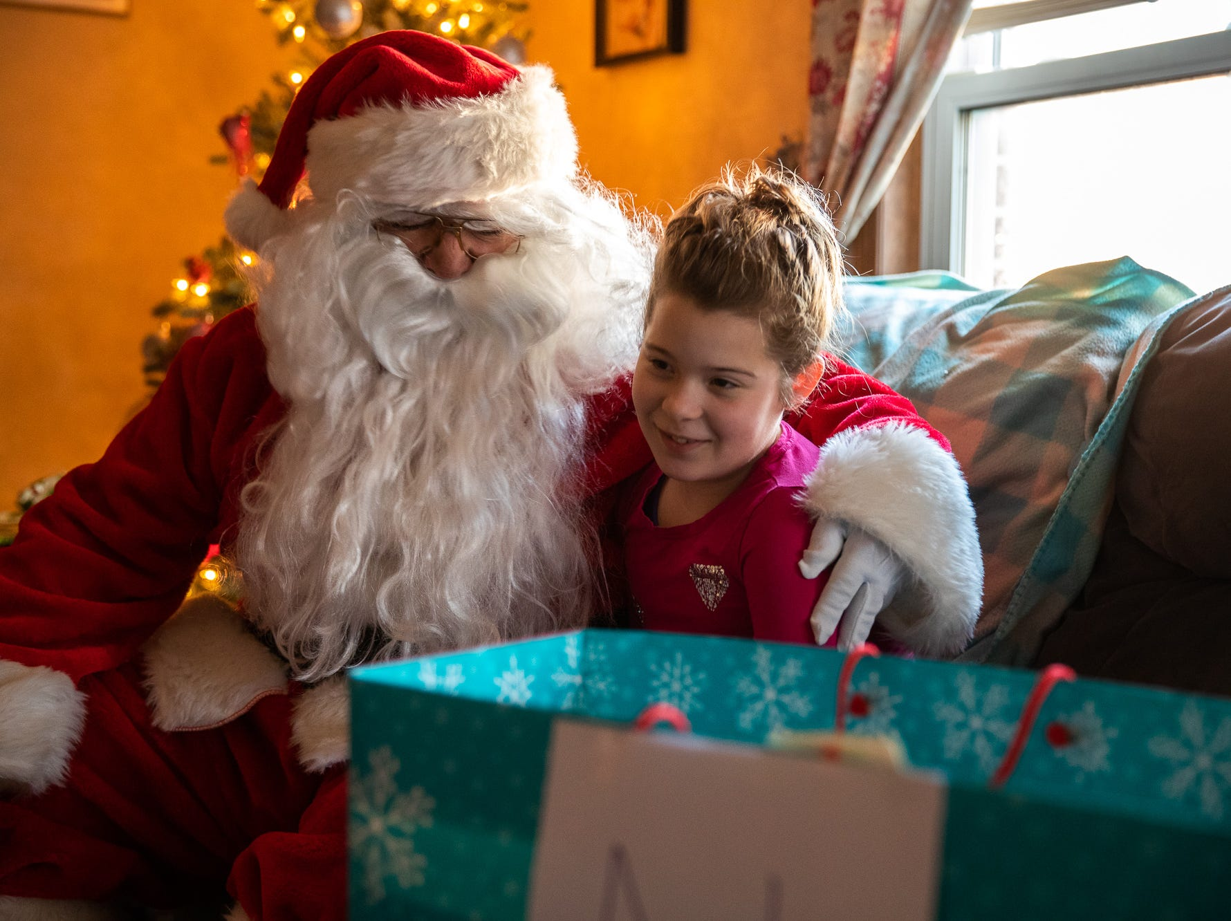 Kiara, who will be 10 tomorrow, sits with Santa, played by firefighter Wayne Reid, during the S.A.V.E.S Project Santa, Saturday, Dec. 22, 2018, in McSherrystown Borough. The S.A.V.E.S Project Santa donated food, toys, and clothing to 12 local families in need.