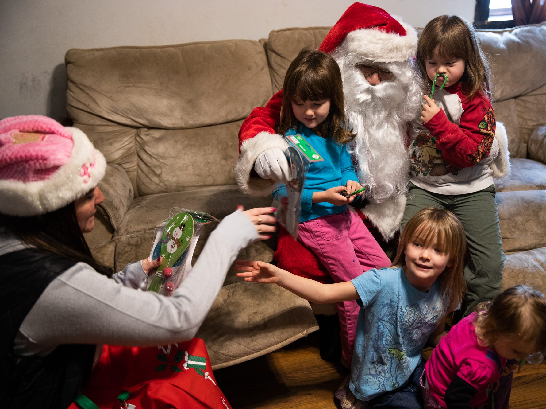 Mia, 4, back left, Sierra, 7, back right, Laila, 6, front left, and Arianna, 2, front right, get presents from Santa, played by firefighter Wayne Reid, during the S.A.V.E.S Project Santa, Saturday, Dec. 22, 2018, in McSherrystown Borough. The S.A.V.E.S Project Santa donated food, toys, and clothing to 12 local families in need.