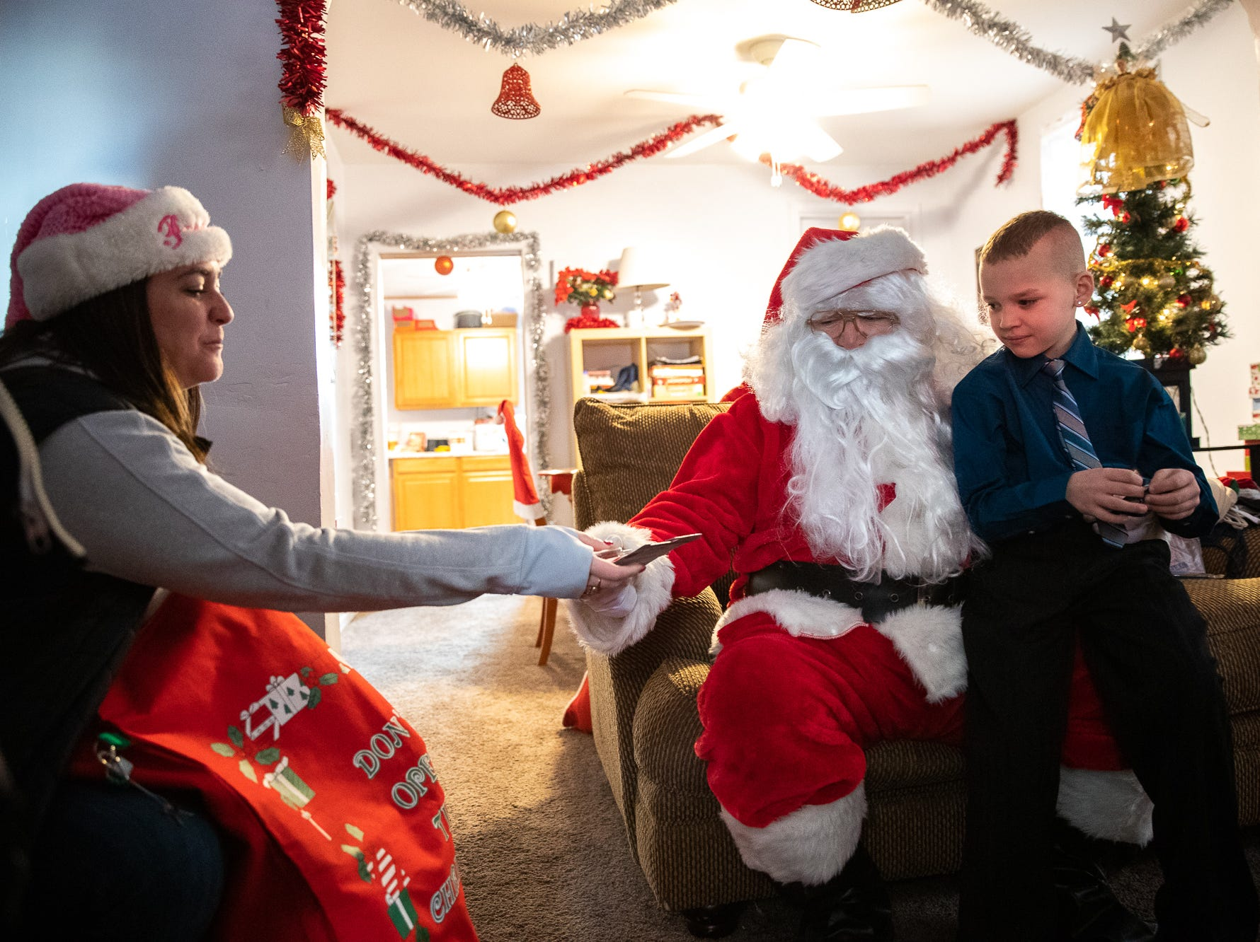 Isaiah, 8, gets presents from Santa, played by firefighter Wayne Reid, during the S.A.V.E.S Project Santa, Saturday, Dec. 22, 2018, in McSherrystown Borough. The S.A.V.E.S Project Santa donated food, toys, and clothing to 12 local families in need.