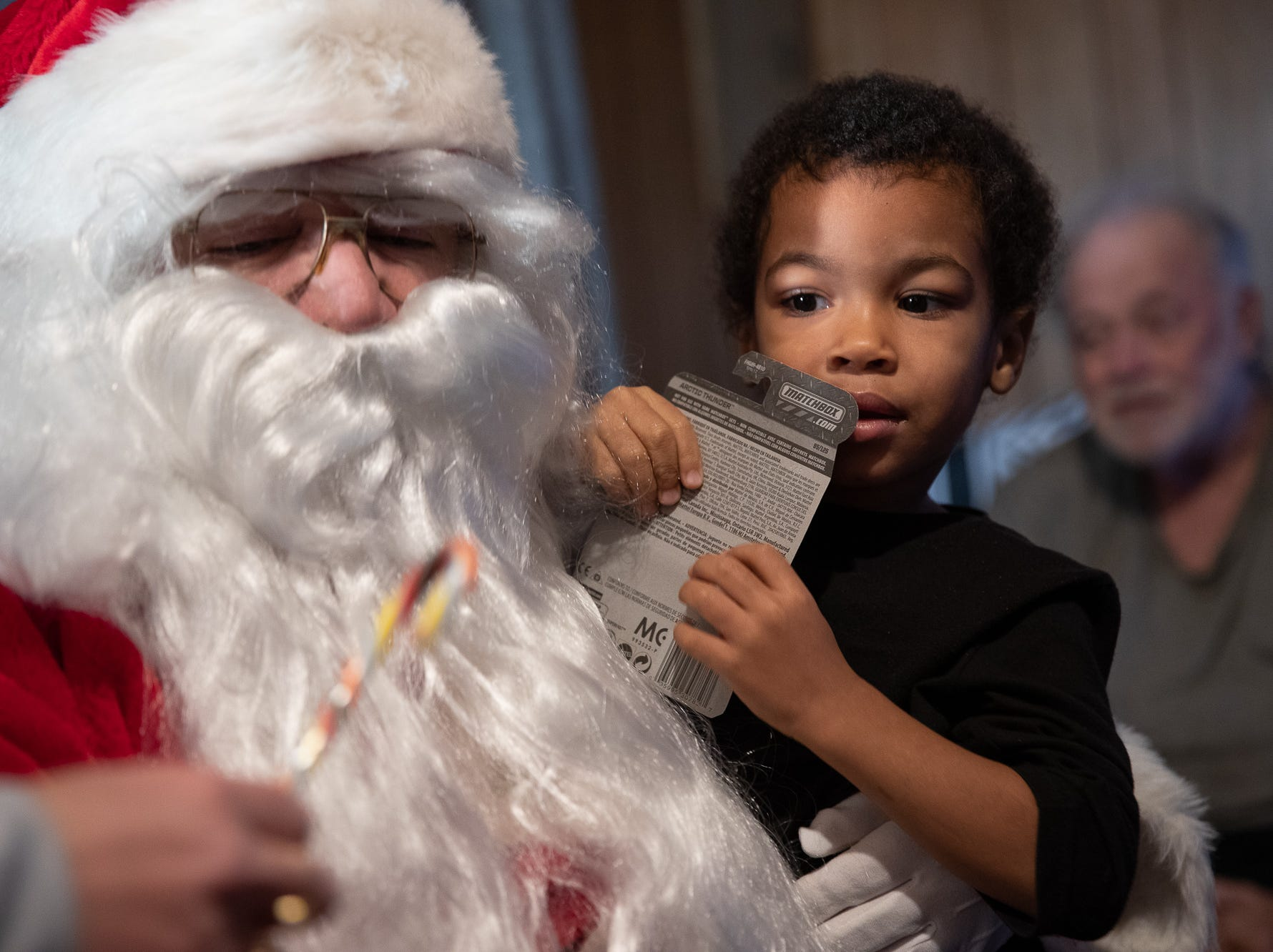 Dae'Ceyion, 3, gets presents from Santa, played by firefighter Wayne Reid, during the S.A.V.E.S Project Santa, Saturday, Dec. 22, 2018, in McSherrystown Borough. The S.A.V.E.S Project Santa donated food, toys, and clothing to 12 local families in need.