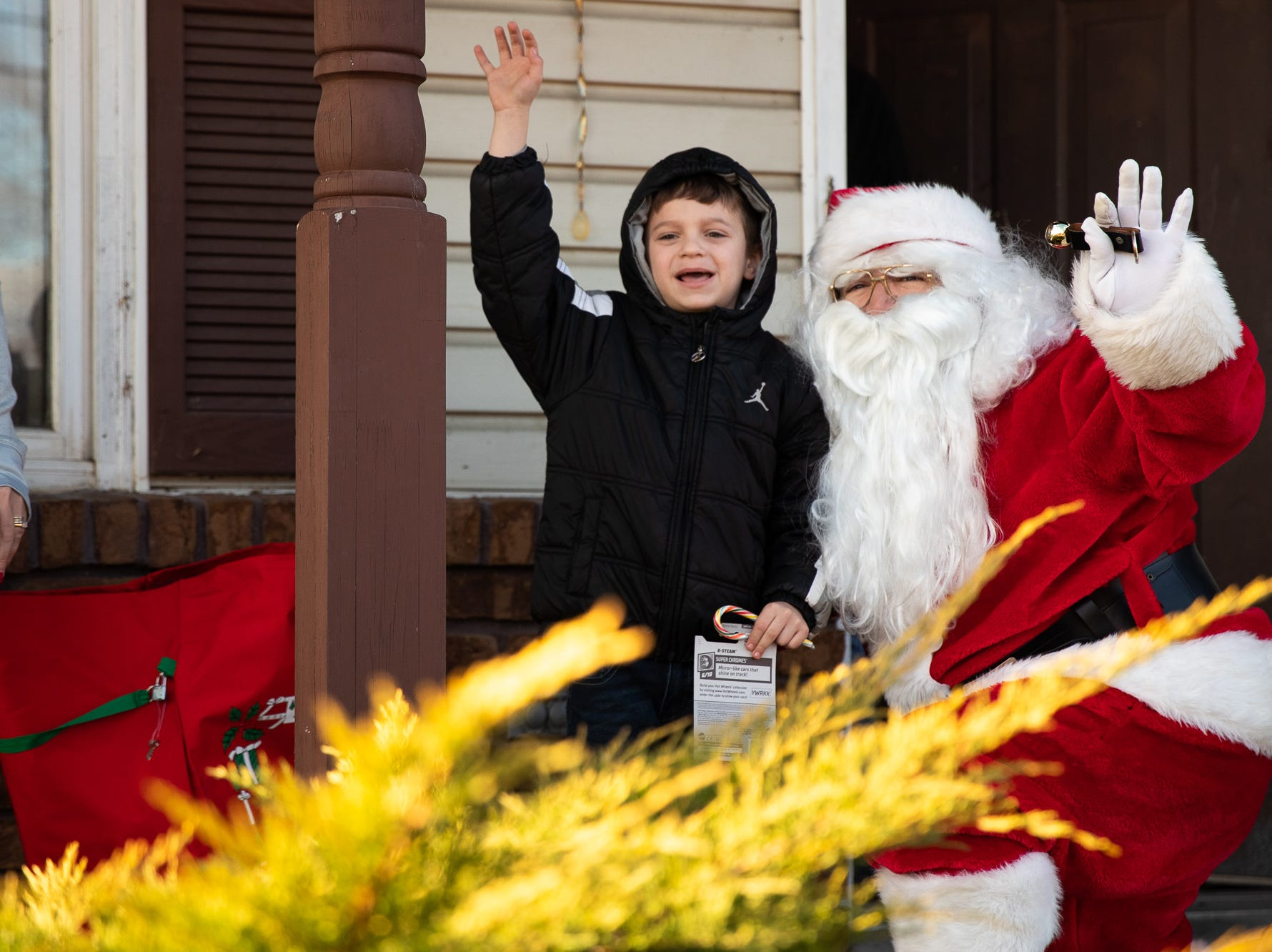 Breiden, 7, waves to the fire engines along with Santa, played by firefighter Wayne Reid, during the S.A.V.E.S Project Santa, Saturday, Dec. 22, 2018, in McSherrystown Borough. The S.A.V.E.S Project Santa donated food, toys, and clothing to 12 local families in need.