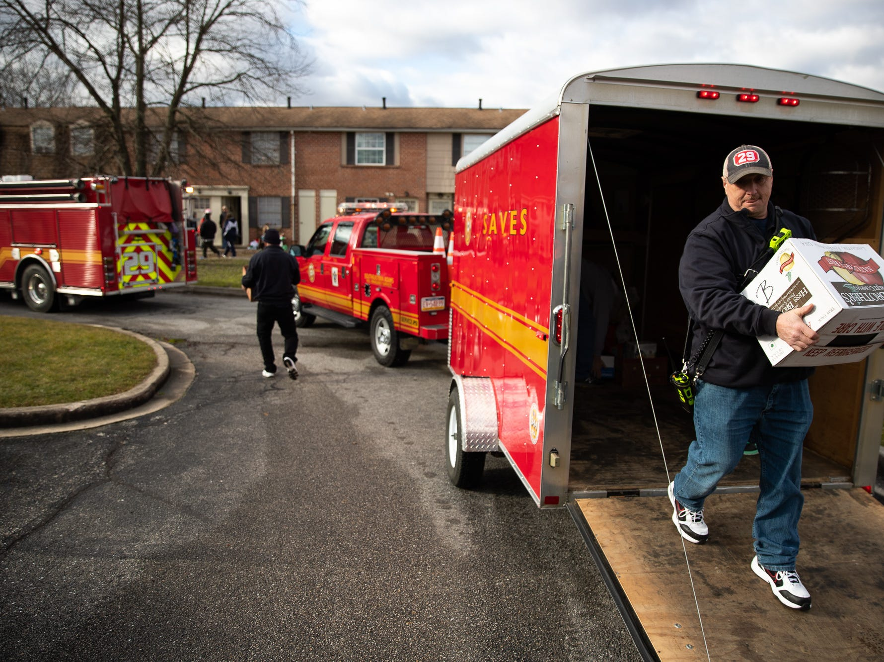 Volunteers carry out presents during the S.A.V.E.S Project Santa, Saturday, Dec. 22, 2018, in McSherrystown Borough. The S.A.V.E.S Project Santa donated food, toys, and clothing to 12 local families in need.