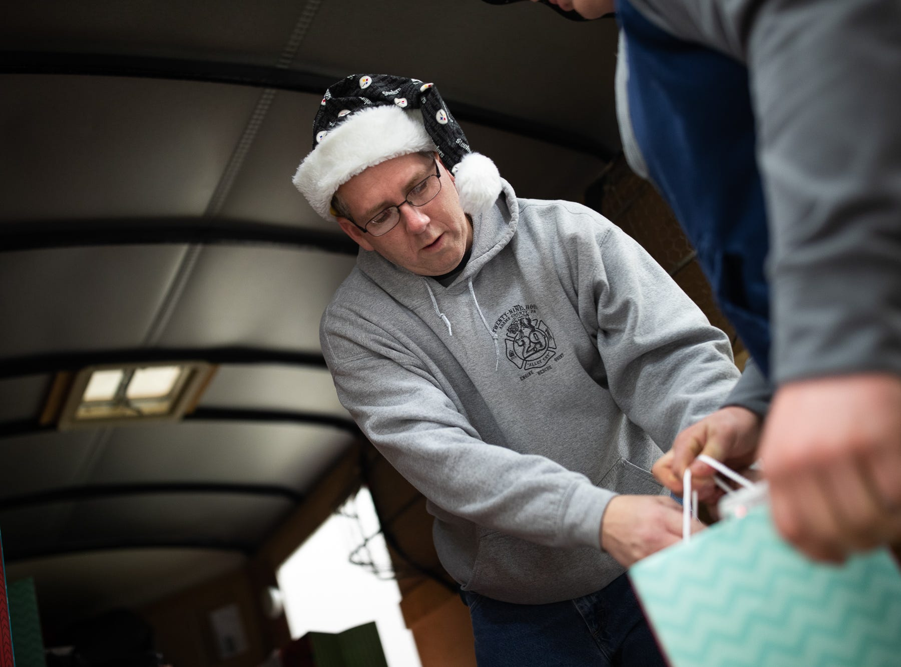 Firefighter Chad Grimes loads presents at the Southeastern Adams County Volunteer Emergency Services fire station during the S.A.V.E.S Project Santa, Saturday, Dec. 22, 2018, in McSherrystown Borough. The S.A.V.E.S Project Santa donated food, toys, and clothing to 12 local families in need.
