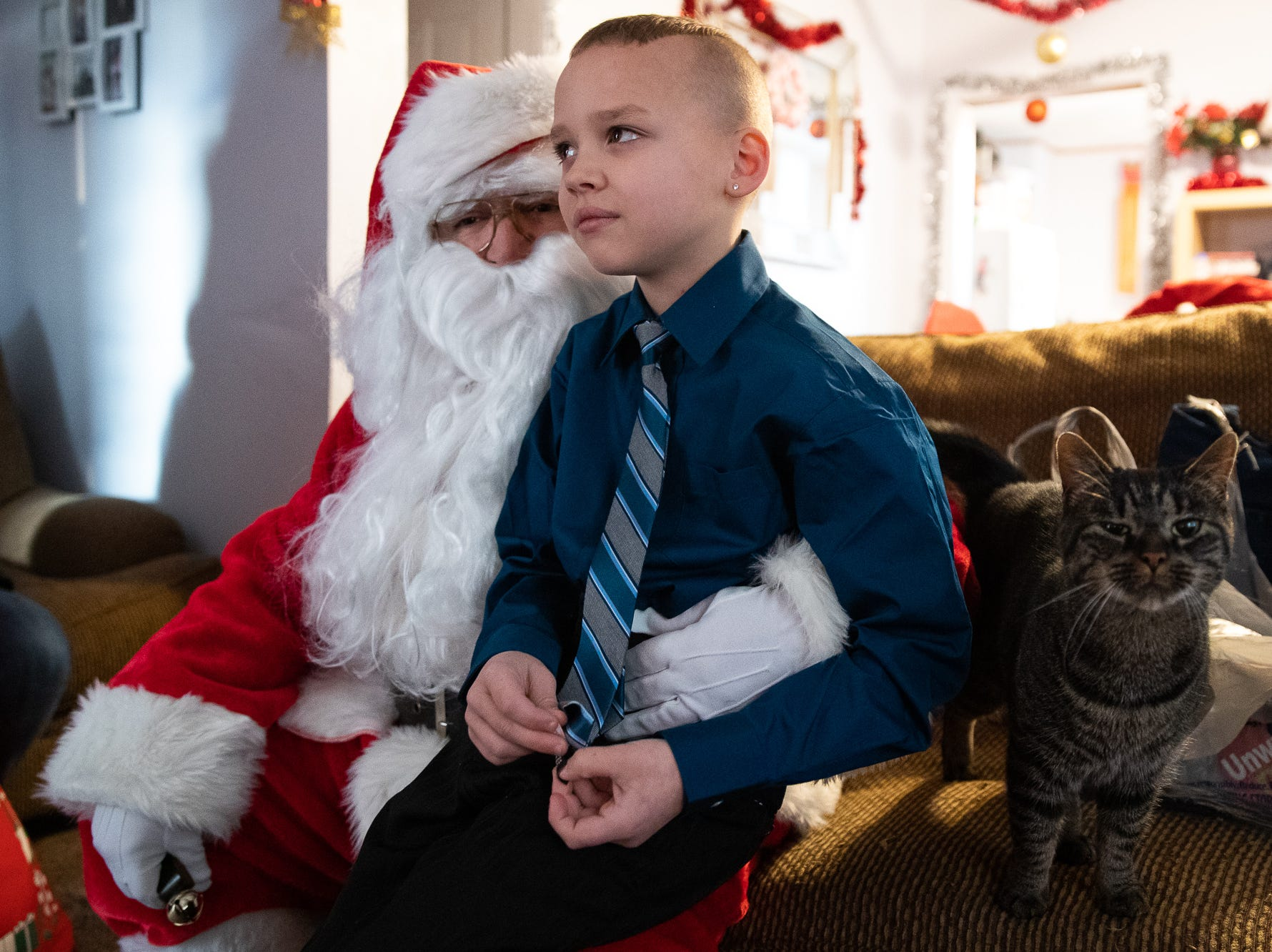 Isaiah, 8, sits on the lap of Santa, played by firefighter Wayne Reid, during the S.A.V.E.S Project Santa, Saturday, Dec. 22, 2018, in McSherrystown Borough. The S.A.V.E.S Project Santa donated food, toys, and clothing to 12 local families in need.
