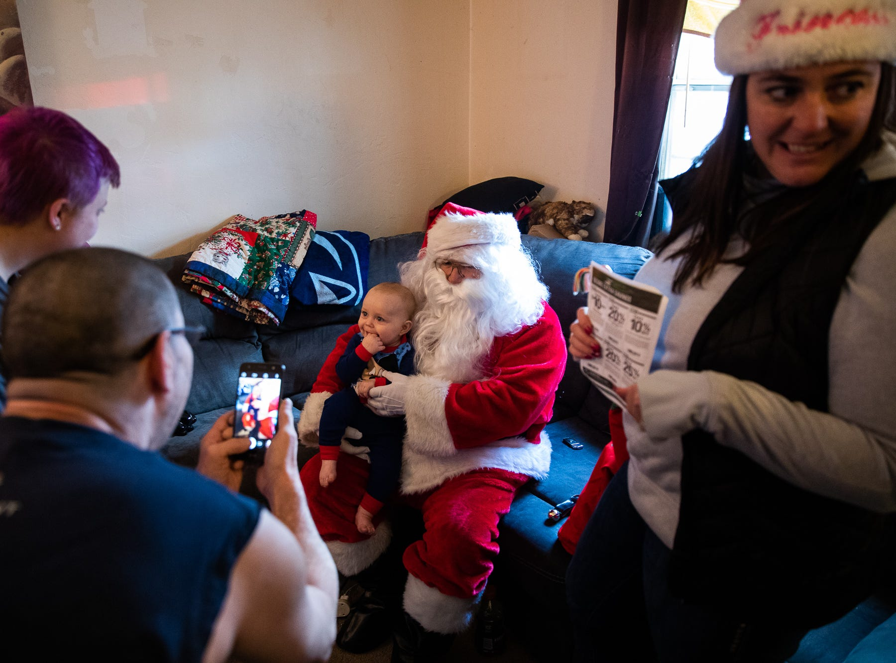 Family members take photos as 7-month-old Heath sits on the lap of Santa, played by firefighter Wayne Reid, during the S.A.V.E.S Project Santa, Saturday, Dec. 22, 2018, in McSherrystown Borough. The S.A.V.E.S Project Santa donated food, toys, and clothing to 12 local families in need.