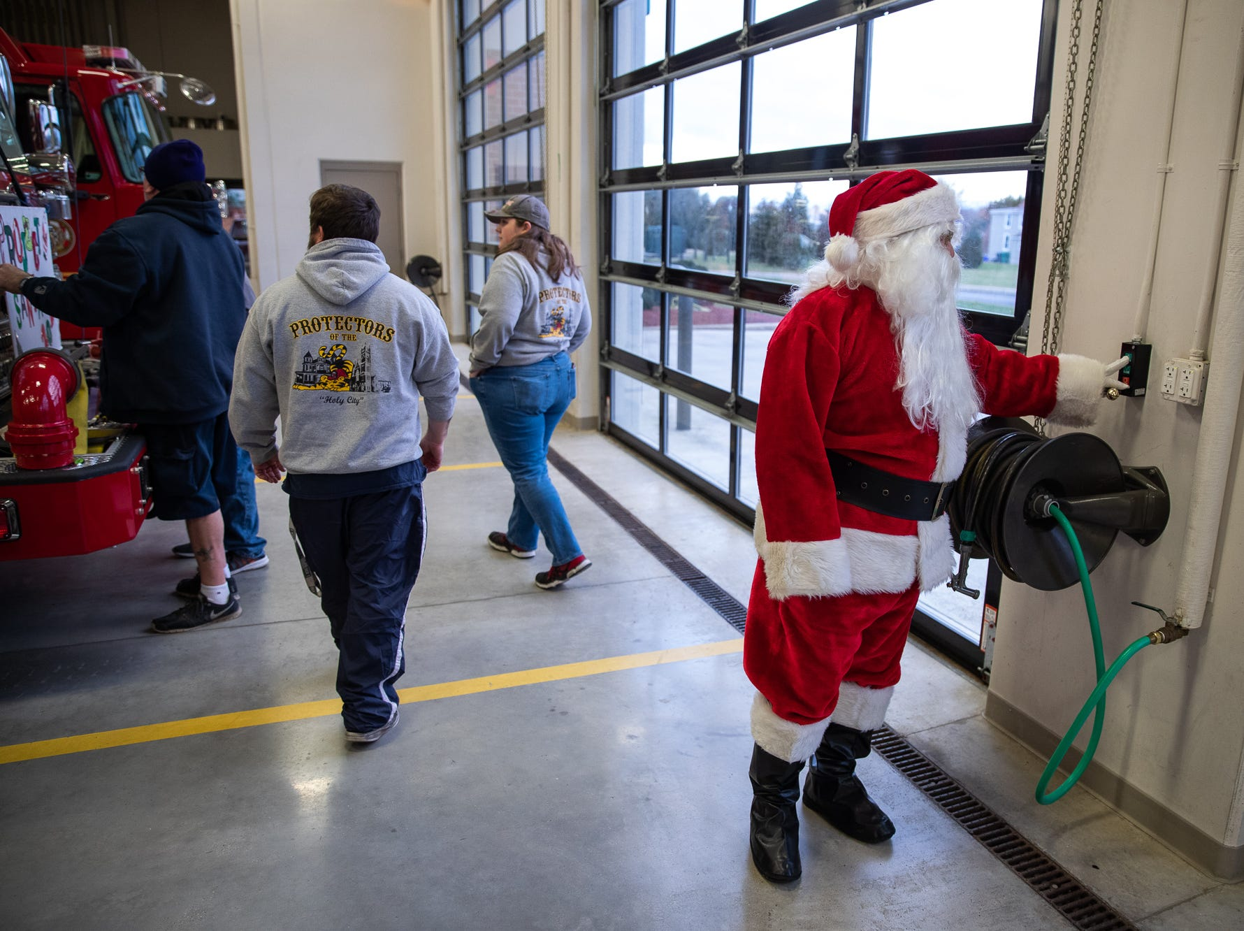 Santa, played by firefighter Wayne Reid, opens the bay doors of the Southeastern Adams County Volunteer Emergency Services fire station during the S.A.V.E.S Project Santa, Saturday, Dec. 22, 2018, in McSherrystown Borough. The S.A.V.E.S Project Santa donated food, toys, and clothing to 12 local families in need.