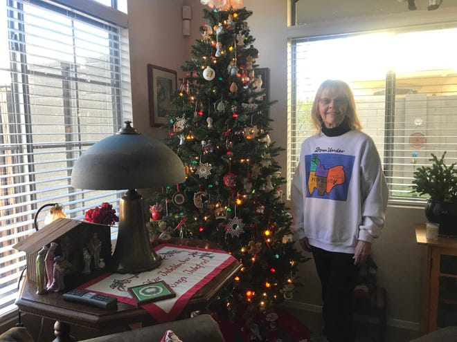 Cathy Matlock, a homeowner in The Pinnacle at Desert Peak condominium complex, poses with her Christmas tree on Dec. 22, 2018.