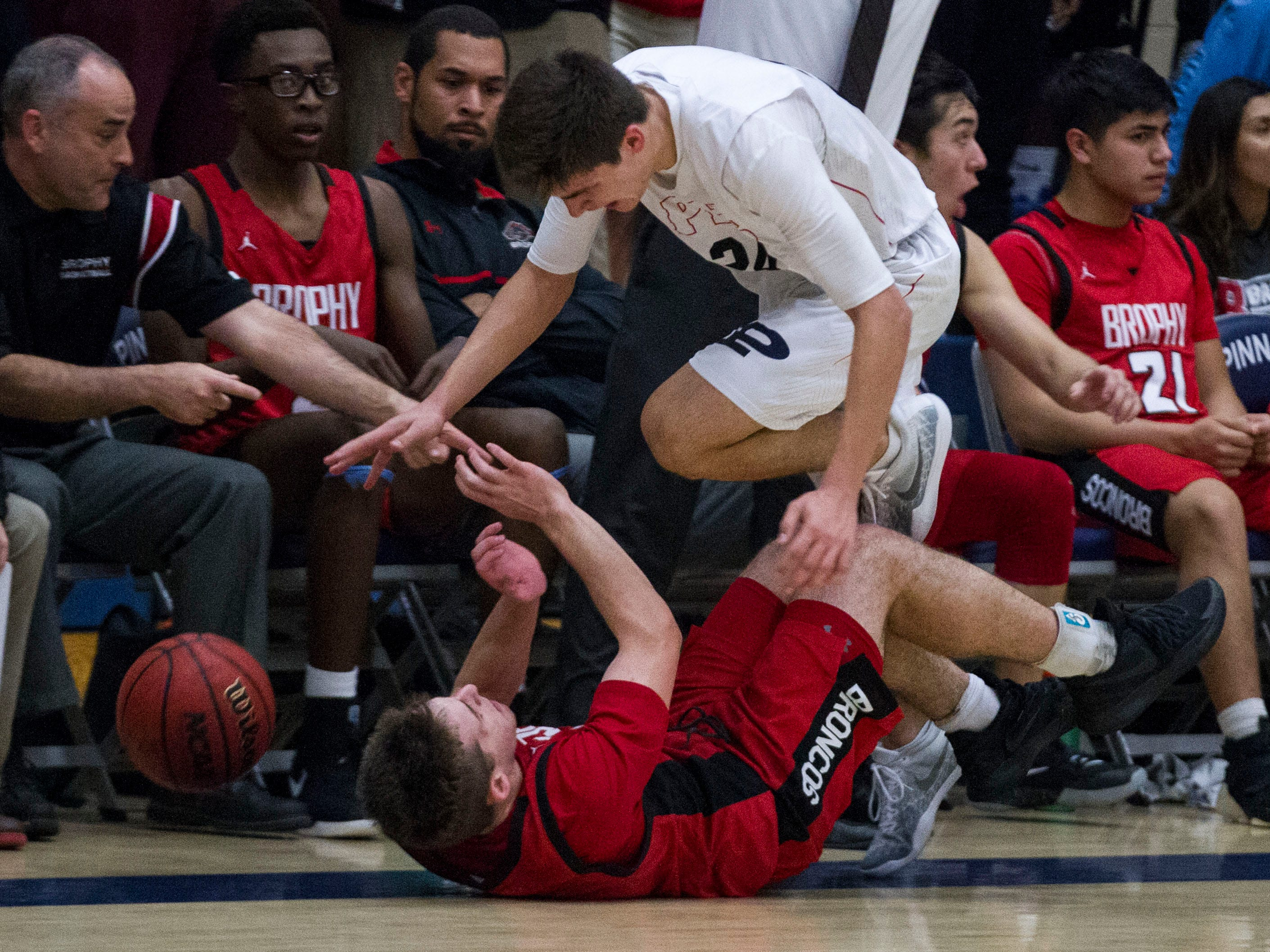 Pinnacle's Trent Brown (24) trips over Brophy's Ryan Gilburne (3) during their game in Phoenix, Friday, Dec. 21, 2018.