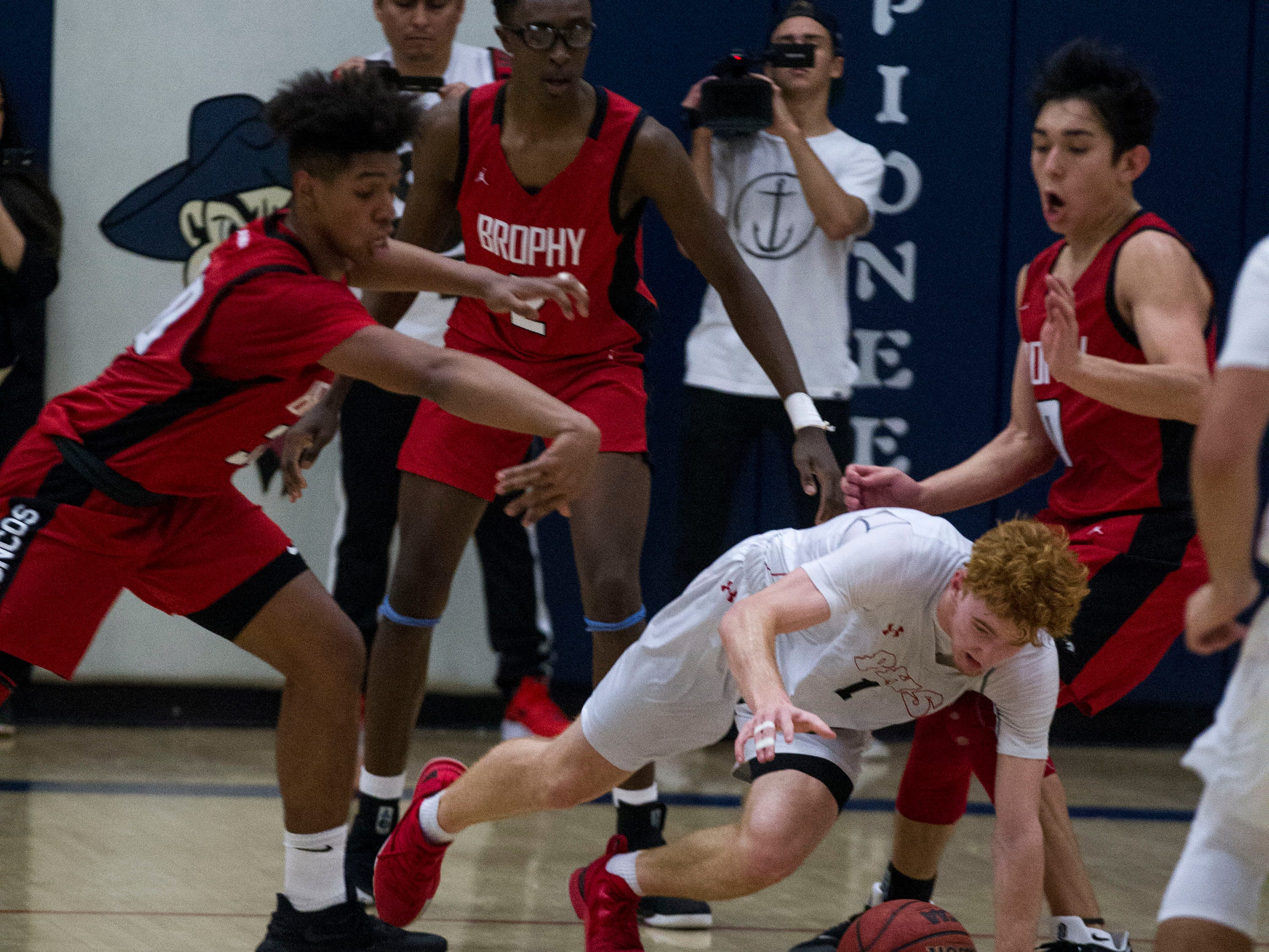 Pinnacle's Nico Mannion (1) gets out of trouble after being surrounded by three Brophy players during their game in Phoenix, Friday, Dec. 21, 2018.