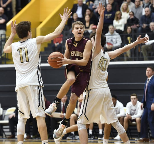 Pittsford Mendon's Jacob Shadders, center, splits the defense of Pittsford Sutherland's John Messina (11) and Kevin Ryan during the 18th Annual Rainbow Classic on Friday, Dec. 21, 2018. Mendon beat Sutherland 61-57.