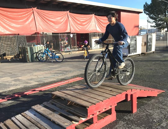 Johnathan Powers tries out his new bike  Friday afternoon at the Chain Gang Bike Shop. The boy lost his bicycle in the Carr Fire and the Redding bike shop arranged to give him a new one.