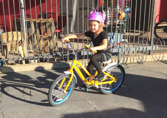 Jeanette Lievsay, 6, rides her new bike at the Chain Gang Bike Shop in Redding on Friday afternoon. She's one of about 50 youngsters who received free bikes to replace the ones destroyed by the Carr Fire.