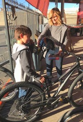 Jaxon Lievsay, left, is handed a helmet by Chain Gang Bike Shop co-owner Angie James as the boy holds onto his new bike Friday afternoon.