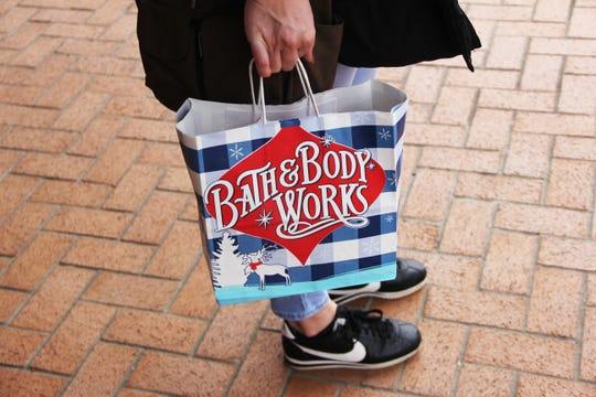 Ali Morrison, of Salem, holds a Bath & Body Works bag outside of Salem Center on Saturday, Dec. 22.
