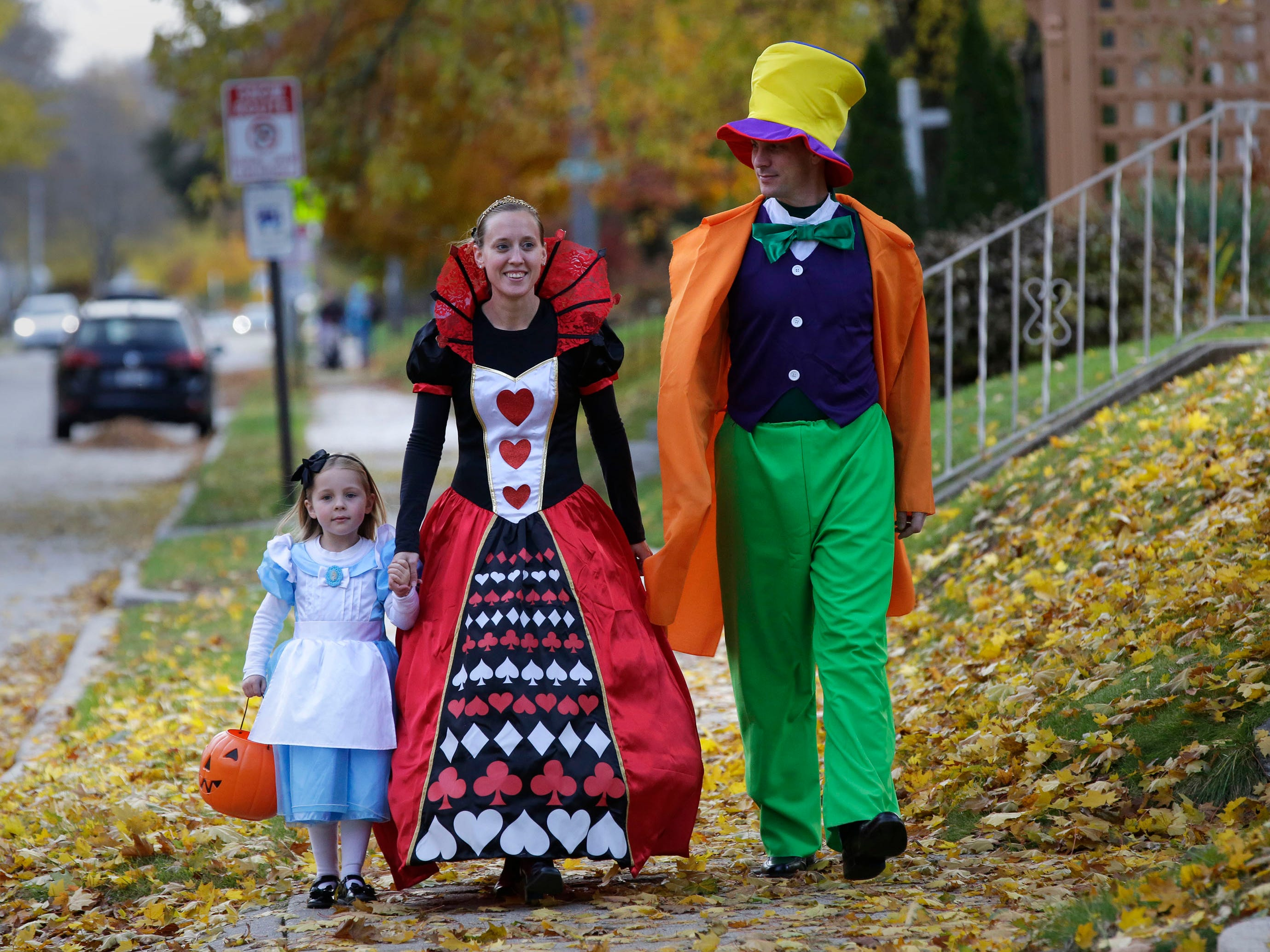"Audrey Wiltzius, 5, walks with her parents Tayna and Robert dressed as characters from ""Alice in Wonderland"" along North 6th Street during Trick or Treat, Wednesday, October 31, 2018, in Sheboygan, Wis."