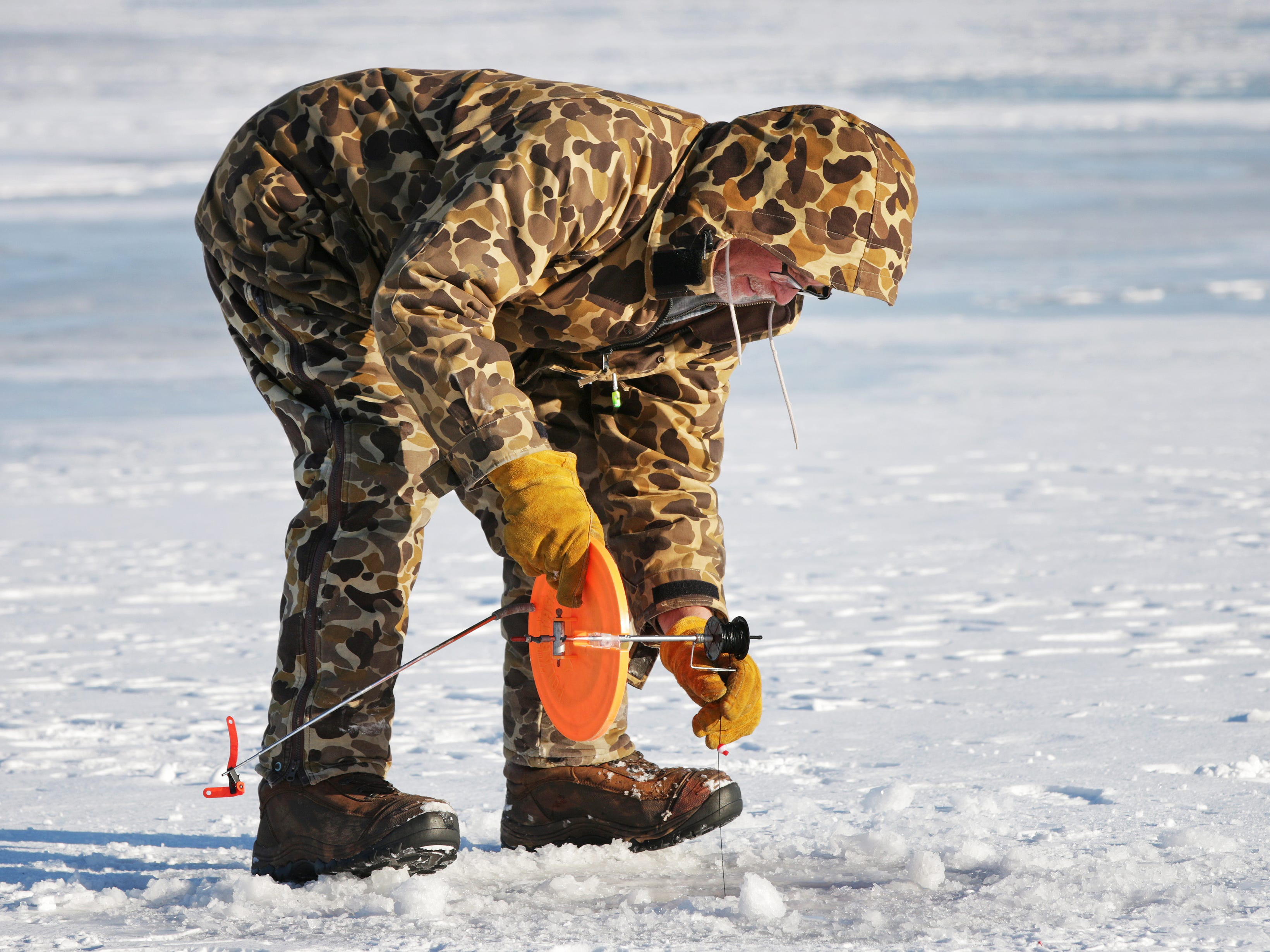 Jeff Krenke of Port Washington, Wis., sets his tip up, Tuesday December 26, 2017, at Random Lake, Wis.  The well bundled Krenke said he didn't catch anything yet, but he had hopes to before leaving.
